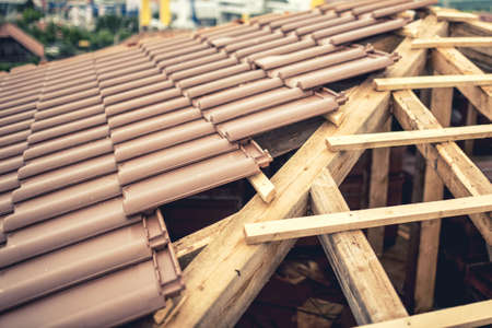 briks: Construction site of new house roof building with brown tiles and timber. Contractor building roof of new house Stock Photo