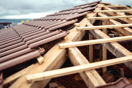 Roof under construction with stacks of brown modern tiles covering house Stock Photo