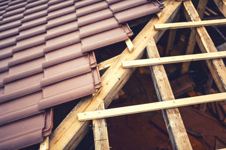 briks: Roof building with ceramic brown tiles on wooden timber structure. Geometric distribution of roof tiles at new house construction Stock Photo