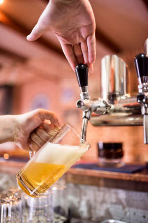 draught: Barman at bistro or pub pouring lager and unfiltered beer in glass
