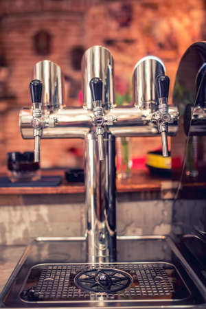 Beer taps at restaurant bar pub or bistro. Closeup details of beer draft taps in a row on barman counter in bar photo