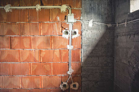 electric lines construction at new estate electricity pipes and brick walls under construction 写真素材