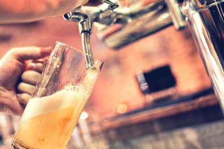 cerveza: Mano del camarero verter una gran cerveza lager en grifo Foto de archivo
