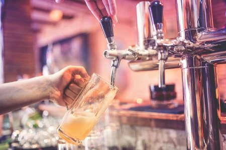cerveza: primer plano de hombre de barman mano en el grifo de cerveza verter una cerveza cerveza de barril en el restaurante pub o restaurante