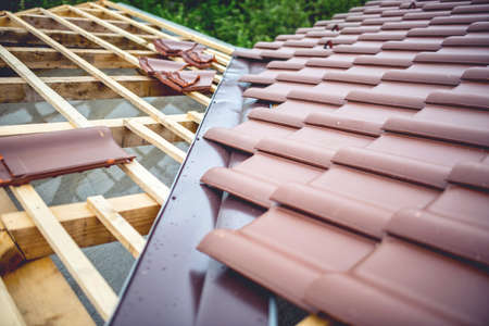 Roof building at new house construction. Brown roof tiles covering estate