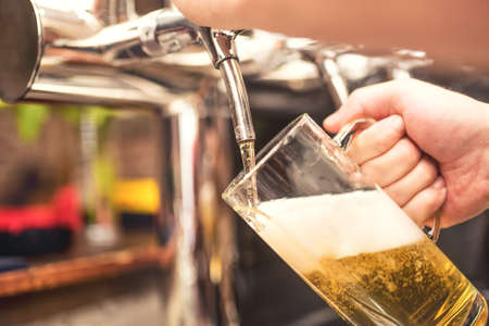 serving: bistro waiter serving a cold chill beer. Hand of barman pouring a lager beer from tap Stock Photo