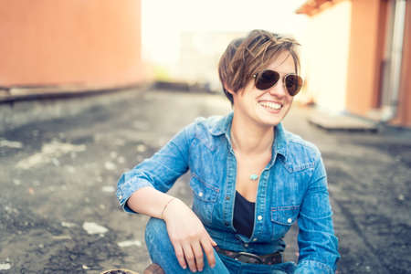 portrait of beautiful girl with sunglasses laughing and smiling while talking with friends, hanging out on roof of building. Young active lifestyle people concept Reklamní fotografie