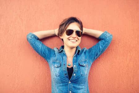 confianza: Chica morena de moda, haciendo expresiones de la cara, sonriendo y riendo contra el fondo naranja, aislado. Estilo de vida moderno con la chica inconformista hermosa con gafas de sol Foto de archivo