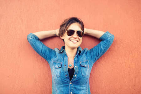 confidence: Trendy brunette girl, making face expressions, smiling and laughing against orange background, isolated. Modern lifestyle with beautiful hipster girl with sunglasses