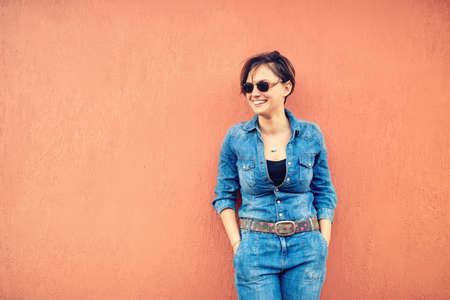 fashion lifestyle with beautiful funny woman on terrace wearing modern jeans outfit, sunglasses and smiling. Stock Photo