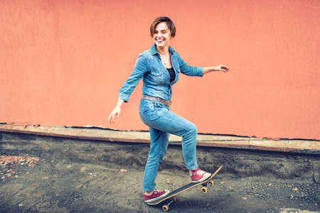artsy: Artsy portrait of a brunette cute girl on a skateboard, laughing and having a good time. Healthy concept of modern life, hipster girl with skateboard on rooftop
