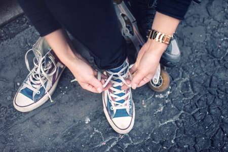 female clothing: Hipster wearing sneakers, teenager tieing laces at sport shoes. Urban lifestyle with footwear and modern clothing.