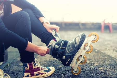 Gelukkig jong meisje genieten van rolschaatsen, skaten, zetten op rollerskates na de activiteiten. Vintage effect op foto