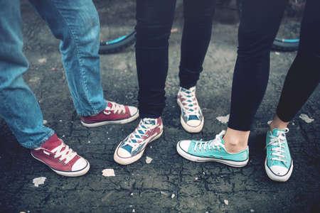 stile: Giovani adolescenti ribelli indossando scarpe da tennis casuali, camminando sul cemento sporco. Scarpe di tela e scarpe da ginnastica per adulti di sesso femminile