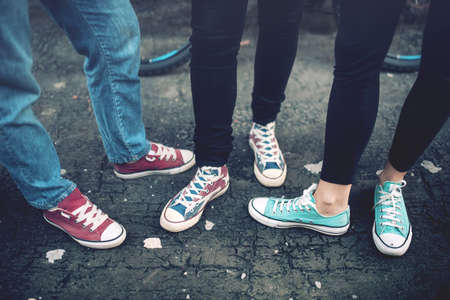 life style: Young rebel teenagers wearing casual sneakers, walking on dirty concrete. Canvas shoes and sneakers on female adults