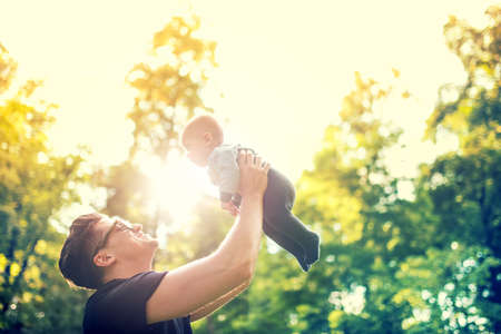 summer day: happy father holding little kid in arms, throwing baby in air. concept of happy family, vintage effect against light