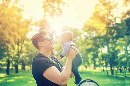 dia soleado: Padre joven que detiene delicado bebé recién nacido en brazos al aire libre en el parque. Concepto de crianza feliz, el día y la familia del padre