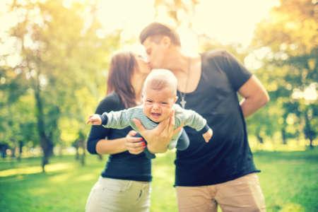 papa y mama: Pareja joven se cas� con la celebraci�n de reci�n nacido y besos. Familia feliz, el padre de y el concepto de d�a de la madre. Foto de archivo