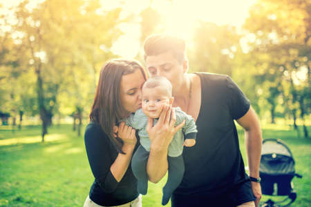 Mommy and daddy holding baby, 3 months old newborn and kissing him. Happy family with father, mother and infant. Vintage effect on photo