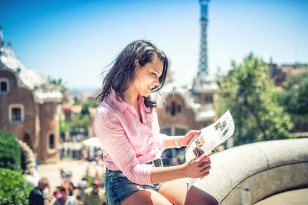 student travel: Pretty attractive girl studying map while traveling on a sunny day. Travel concept with beautiful woman on rooftop building with casual, stylish clothes and map