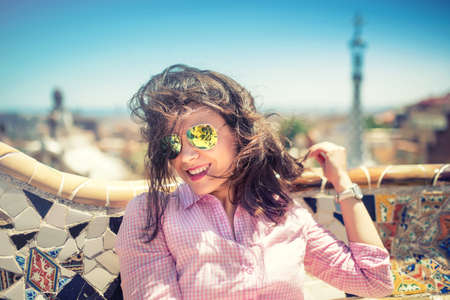 Portrait of smiling, gorgeous brunette girl with sunglasses on a windy day. Beautiful woman smiling and playing with hair on rooftop of building