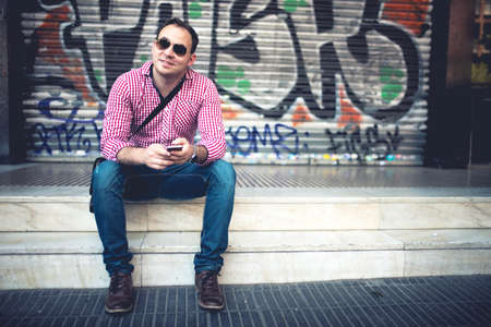 uomini belli: Ritratto di uomo bello con il telefono in mano, casualmente vestito con camicia, jeans e occhiali da sole contro graffiti parete dipinta. Uomo europeo alla moda viaggiare e scattare foto con il cellulare