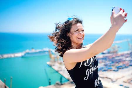 vie sociale: I love selfie! portrait de la belle fille brune de prendre des photos d'elle-m�me, selfies, sur le rivage de la mer. concept moderne de la vie sociale