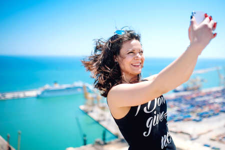 social life: I love selfie! portrait of beautiful brunette girl taking photographs of herself, selfies, on the shore at seaside. modern concept of social life