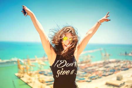 vida social: chica atractiva que llevaba tanque top negro de sonreír, reír y tomar fotos con la cámara del teléfono. Concepto de viaje con la mujer feliz. efecto suave colorido de la foto