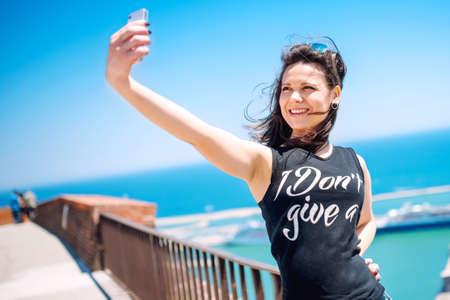 vida social: Amar a tomar fotos de sí misma, niña sonriente y ser feliz mientras que hace autofoto. Foto de archivo