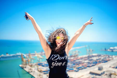 Attractive girl wearing black tank top smiling, laughing and taking pictures with camera phone. Traveling concept with happy woman. Archivio Fotografico