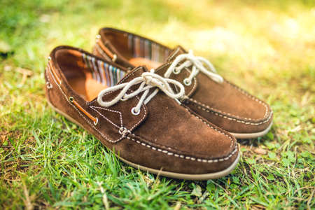 moccasins: Modern brown leather mens shoes, elegant summer moccasins in grass. Men fashion, men accesories and footwear. Stock Photo