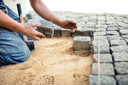 construction worker placing stone tiles in sand for pavement, terrace. Worker placing granite cobblestone pavement at local terrace Stockfoto
