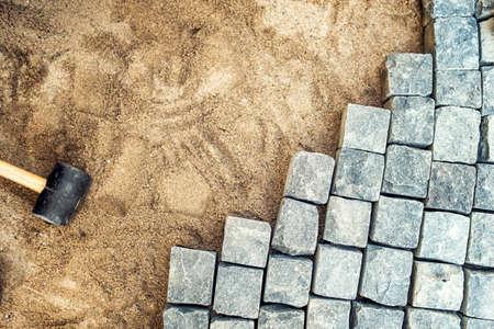 Bouw-instrumenten en details, bestrating installeren en rotsen. Granieten stenen opleggen van zand, maken van de bestrating