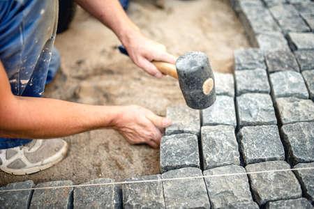 pavement: Worker creating pavement using cobblestone blocks and granite stones