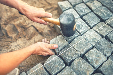 stone road: Close-up of construction worker installing and laying pavement stones on terrace, road or sidewalk. Worker using stones and rubber hammer to build stone sidewalk Stock Photo
