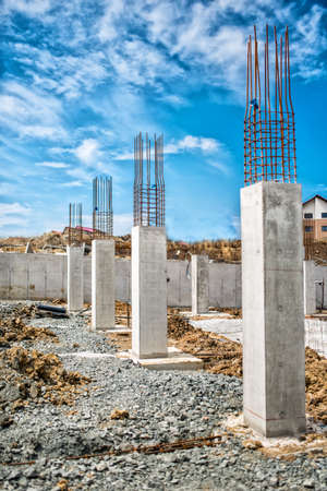 site: Reinforced steel bars on construction pillars, concrete details and beams at buildng site.