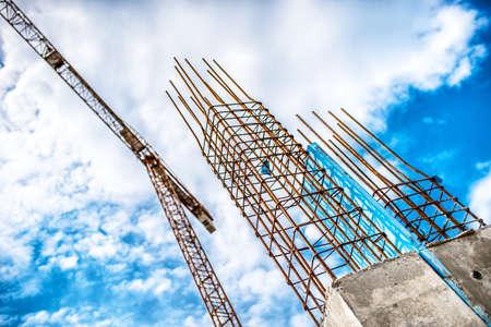 Betonnen pijlers op de industriële bouwplaats. De bouw van de wolkenkrabber met kraan, gereedschappen en versterkte stalen balken