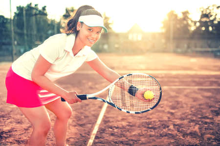 athletic wear: beautiful brunette girl playing tennis with racket, balls and sports equipment. Close up portrait of beautiful woman on tennis court with athletic wear and smiling Stock Photo