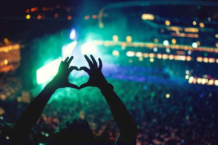 saint valentin coeur: En forme de coeur mains lors d'un concert, d'aimer l'artiste et le festival. Concert de musique avec des lumi�res et silhouette d'un homme jouissant de concert