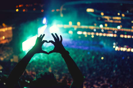 nightclub crowd: Heart shaped hands at concert, loving the artist and the festival. Music concert with lights and silhouette of a man enjoying the concert