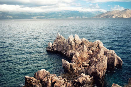 speedboats: Island cliffs and seascape, aerial view with calm sea and clear sky. Soft, vintage effect on photo Stock Photo