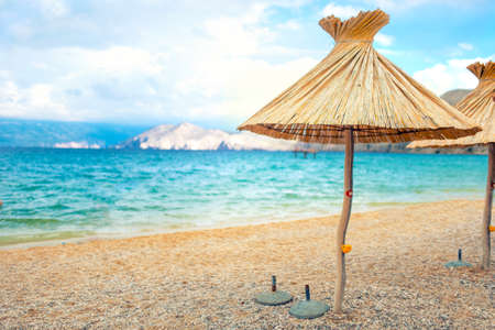 deserted: beach straw umbrella lounger chair with sand and clear water. Sea mediteraneean coastline landscape Stock Photo
