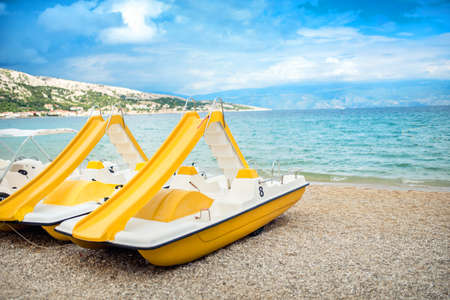 peddle: Beach paddle yellow boats, vacation fun details. Rental paddle boats on shore, on beach in exotic resort Stock Photo