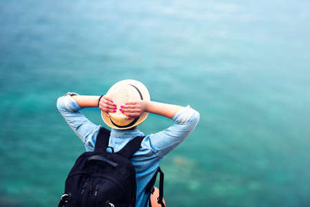 adventure holiday: young woman on summer vacation, hiking on coastline and staring at sea wearing hat and backpack. Travel and adventure concept