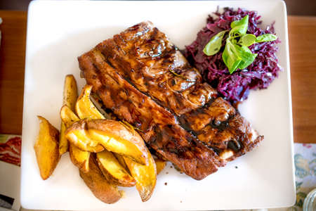 manjar: Barbecue pork ribs as main dish at restaurant. Pork delicacy with delicious barbecue sauce, parsley, cabbage and potatoes Foto de archivo