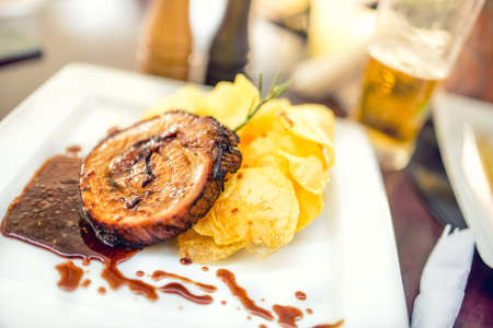 main course: Pork chop on grill with chips as main course at local restaurant, fancy dish from international cuisine