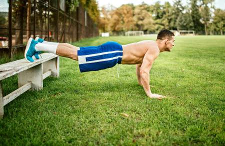 muscle training: atheltic gebaut Mann tun Liegestütze und Core-Training im Park. Fitness Basketball-Spieler Training auf Gras Lizenzfreie Bilder