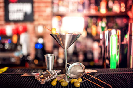 bar tool: alcoholic drink on bar counter. Dry martini with ice and olives, served cold in restaurant, bar or pub.