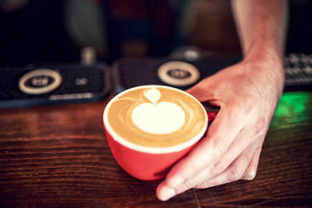 crema: Barman and barista creating latte art with milk foam on fresh coffee. Espresso strong coffee with milk served at restaurant Stock Photo